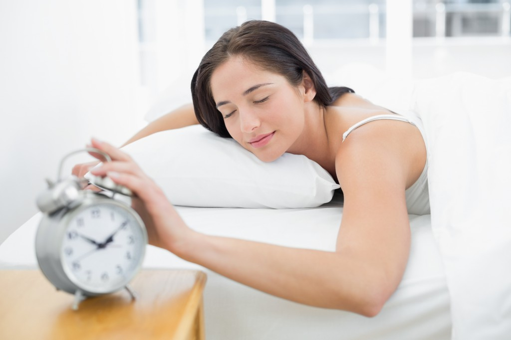 Young woman in bed extending hand to alarm clock at home