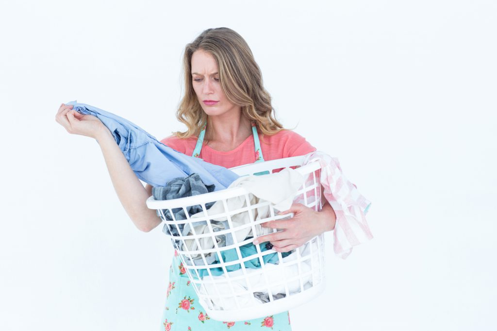 Woman looking at dirty clothes on white background