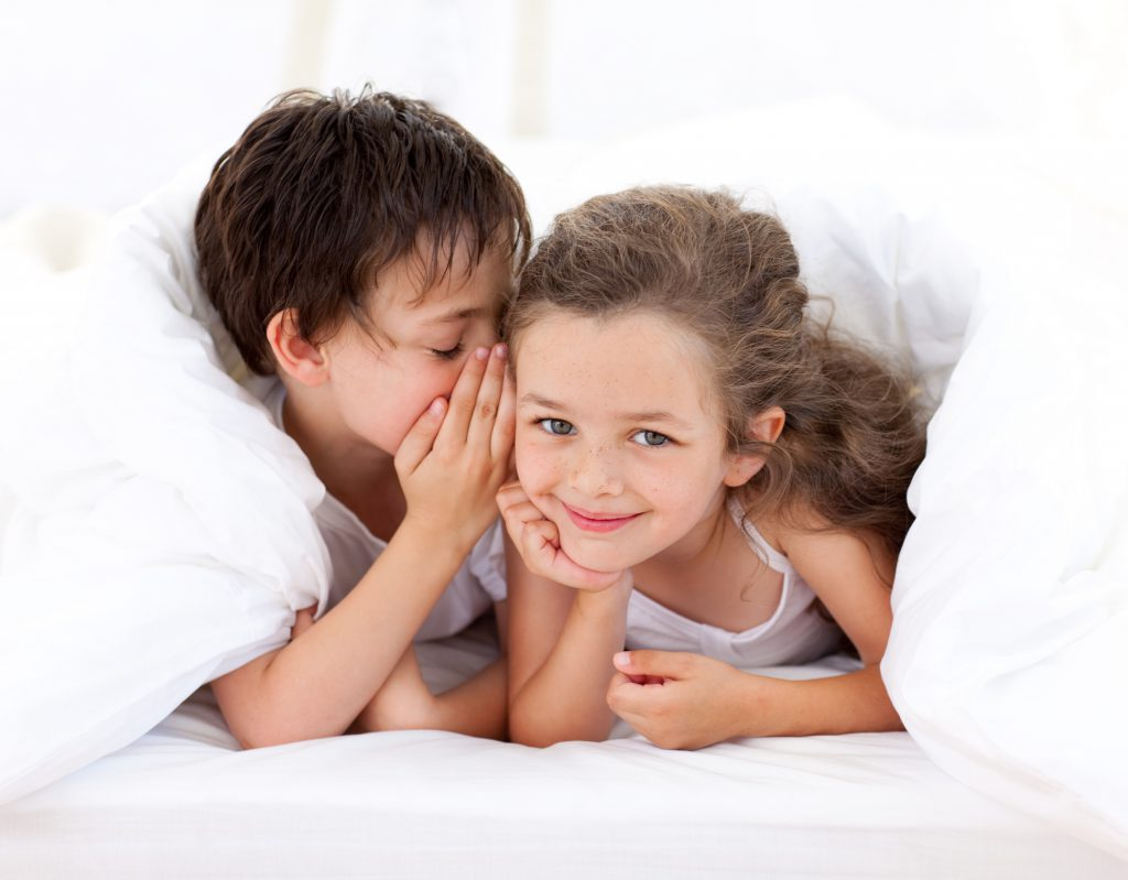Little boy telling a secret to his sister